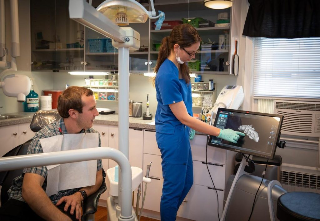 Dental Hygienist explaning 3d dental image to the patient